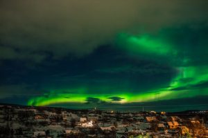 Nothern light over small villag at night. Aurora Borealis